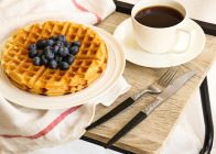 A plate of waffels and a cup of coffee for breakfast.